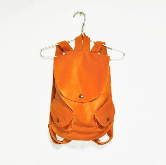A basic velvet backpack with two external snapped pockets. Has soft orange colour. Very nice to touch.  Sizes: Height: 15,7 / 40 cm Width: 11.8 / 30 cm