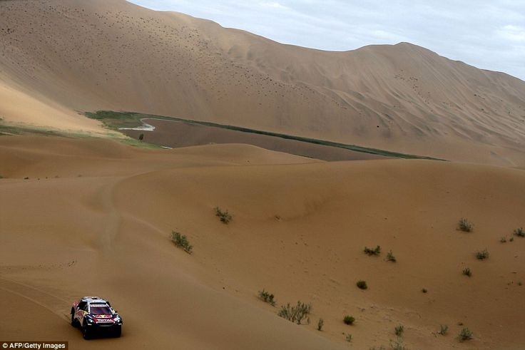 Peugeot team driver Cyril Despres and co-pilot David Castera drive by another smaller oasis in the desert