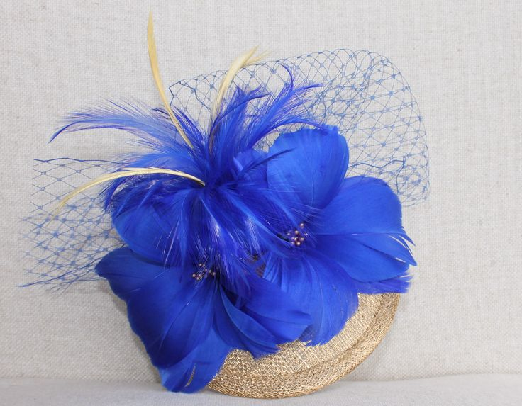 Tocado Jaca: Base, flores de plumas, pomo de plumas y velo en azul real.