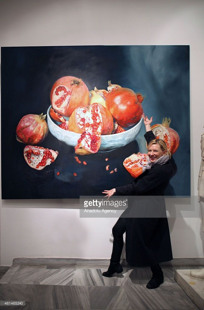 Australian actress Cate Blanchett poses in front of a painting of Turkish painter Ismail Acar at his studio on January 11, 2015 in Istanbul, Turkey.