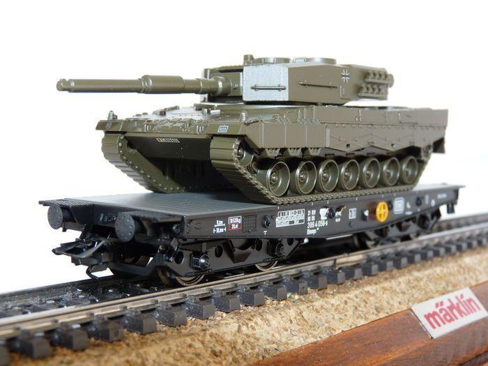 Trix H0 - 24211.02 - 4MFOR Schwerlastwagen van de beladen met Panzer Leo2  Trix H0 - 24211.02 - 4MFOR Schwerlastwagen van de beladen met Panzer Leo2 Unieke serie. uitverkocht bij Trix. Model: 1 zware vlakwagen van Rlmmps 650 van de Deutsche Bundesbahn (DB) geladen met afhankelijk van een Leopard - 2- tank van de Duitse Bundeswehr. Operatie rond 1980. Model:-Chassis van de auto gemaakt van metaal. Met bewegingssysteem voor korte koppeling en koppeling schoten volgens NEM. Behoud van wiggen…