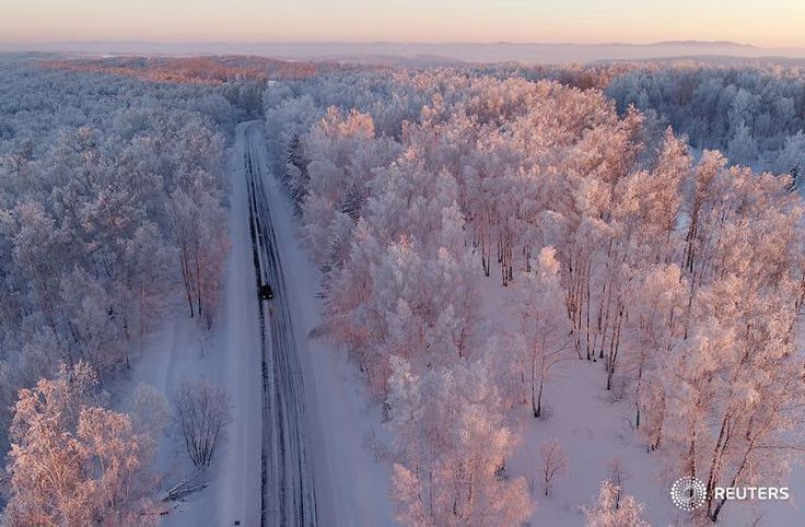 An aerial view shows a car driving along a forest road during sunset, with the air temperature at about minus 27 degrees Celsius (minus 16.6 degrees Fahrenheit), in the Siberian Taiga area outside the village of Balakhta, in Krasnoyarsk region, Russia January 5, 2018. REUTERS/Ilya Naymushin #russia #cold #weather #reuters #reutersphotos #weather #environment #siberia