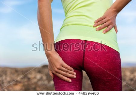 Lower back glute muscle pain cramp athlete runner. Running woman athlete on outdoor trail run holding leg with painful behind injury, strained legs, hurting butt or sore body.
