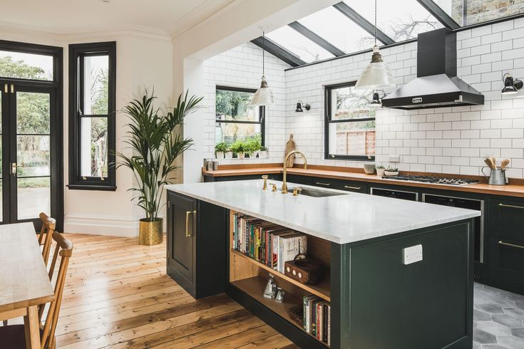 L-shaped kitchen with a central island. The shaker style cabinets with beaded frames are painted in Little Greene Obsidian Green. The handles a brass d-bar style. The worktop on the perimeter units is Iroko wood and Carrara marble in the island. A single sink sits in the island with a polished brass tap. An open book shelf forms part of a breakfast bar. The tiles are flat white metro tiles with a dark grey grout. A Wolf gas hob sits above Neff ovens with a  Falcon extractor hood over the…