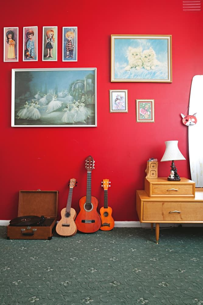 A bright red wall is paired with whimsical art and decor for a wonderful  vintage retro