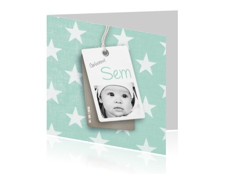 Trendy geboortekaartje voor een jongen met eigen foto, een hip labeltje en pastel mint groene achtergrond met witte sterren.