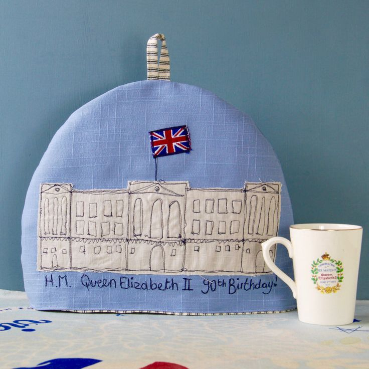 The+Queen's+birthday+-+tea+cosy+-+Size+Approx+in+cm:+28(h)+x+26(dia.)+x+72(cir.)Material+outer+made+from+linen+or+brushed+cotton.+Lining+made+from+baby+cord+or+cotton+ticking.+Padded+with+polyester+wadding.Design+detail+Applique+and+freehand+machine+embroidery+on+front+and+back.+Embellished+with+vintage+1970's+silver+jubilee+ribbon+flag.