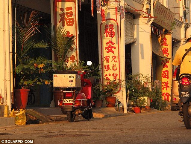 Asia: The Vespa is pictured here parked up outside a colourfully decorated business in Malaka, Malaysia as Mr Milne journeyed through South East Asia