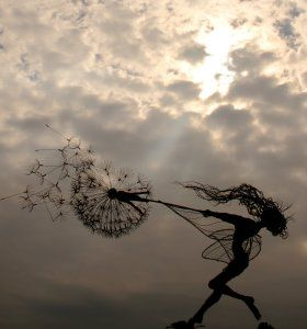 Fantasy Wire Fairies Sculptures. Fairy being blown along by the wind while holding on to a dandelion clock.