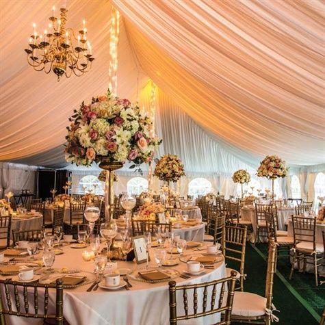 """Lavish Tented Reception...""""Because the reception was in a tent, we had to create the entire look from the ground up,"""" explains Danielle. """"We the created a romantic and elegant feel that I wanted with green turf flooring, a wood dance floor, beautiful draping and glowing chandeliers."""