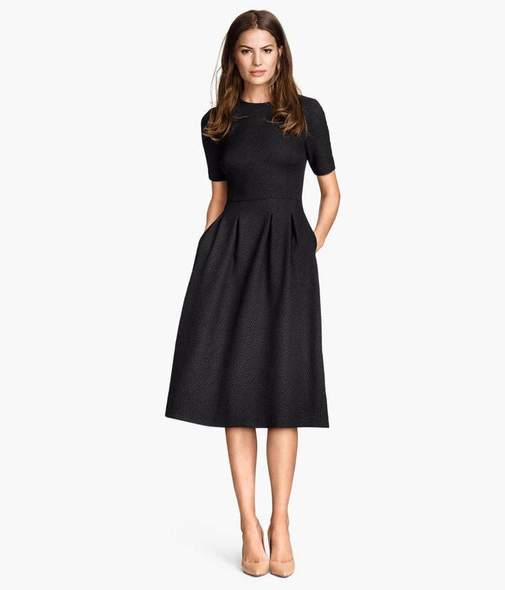 Black. Knee-length dress in textured jersey with short sleeves. Seam at waist, flared skirt with pleats at top, and concealed zip at back. Unlined.