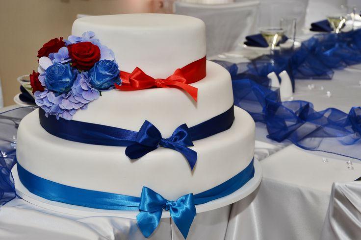 Třípatrový svatební dort, potažený fondánem a dozdoben saténovými stuhami.