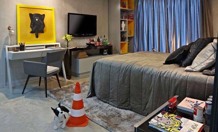 Os móveis usam cores neutras e escuras de maneira predominante, tendo a intensidade do laranja presente nos nichos da estante que valoriza todo o pé direito do espaço.