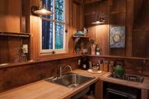 Galley with sink, stovetop, toaster oven, coffee maker, and under-counter fridge/freezer.