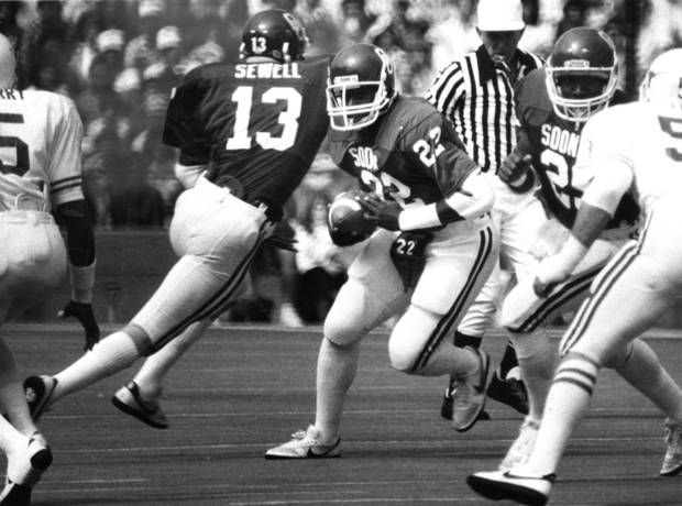 """OU's Marcus Dupree (22) fakes to Steve Sewell, then sets sail on a 63-yard touchdown run"" against Texas in the Cotton Bowl. The Sooners beat the Longhorns 28-22. Staff photo by Jim Argo taken 10/09/82; photo ran in the 10/10/82 Daily Oklahoman. File: Football/OU/OU-Texas/Marcus Dupree/1982"
