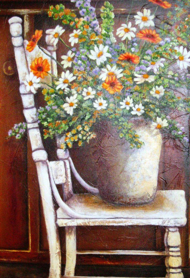 Stella Bruwer large cream urn with daisies and orange flowers on high white shabby chair with wooden cabinet behind it