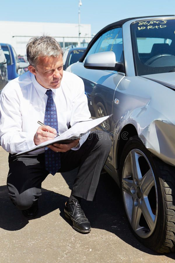 Loss Adjuster Inspecting Car Involved In Accident Male Loss