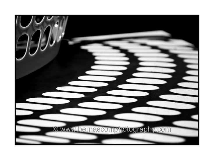 This is a photograph of my washing basket. Yep. My washing basket and some shadow :)    The sun was shining through the basket and I LOVED the pattern it made on the bbq top.    Sometimes the simplest of objects take on a whole new life in a photograph.    I converted the photo to black and white and added some contrast….  by Christine Bernasconi www.bernasconiphotography.com