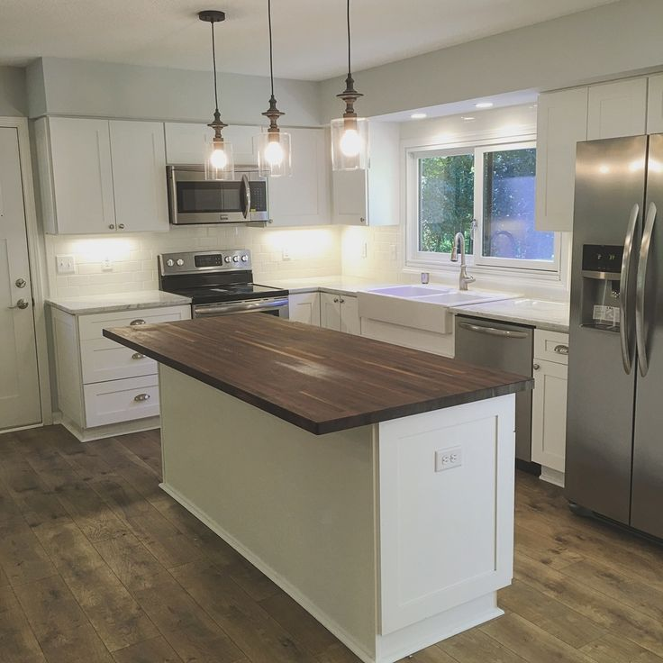 Beautiful white kitchen with shaker cabinets, subway tile backsplash, carerra marble countertops and a walnut butcher block island!
