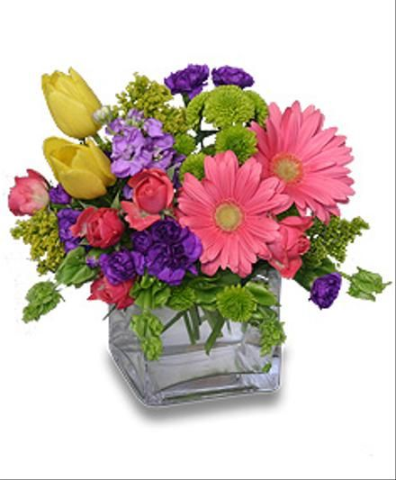 Pretty flower arrangement in a glass cube vase featuring pink gerbera and other flowers that are available for the day of delivery.
