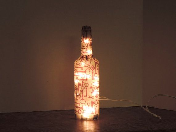 This nightlight is made of a recycled wine bottle with a collage of tissue paper with printed brown keys.