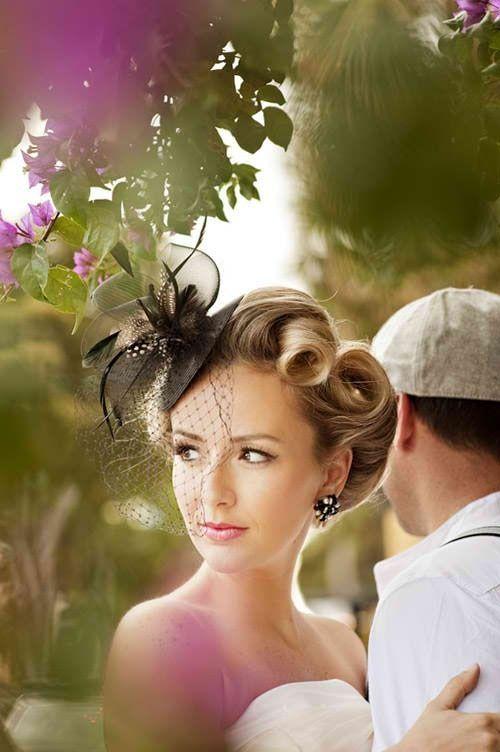 Los bucles decoran este original peinado de novia con tocado en color negro