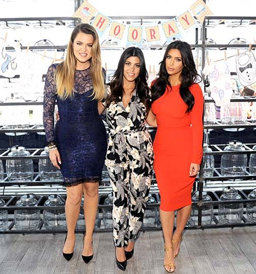 10 of the Best Celebrity Pregnancy Fashion Looks - A pregnant Kourtney Kardashian posed with her sisters while wearing a Kardashian Kollection for Sears jumpsuit.