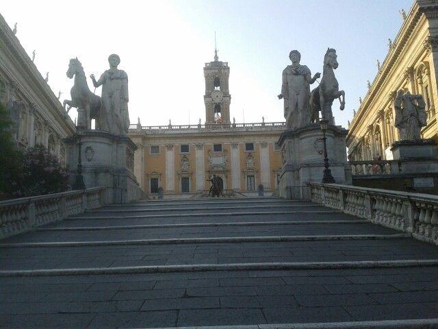 """-Campidoglio Roma- Unha ampla escalinata (""""a Cordonata"""") lévanos ata a Piazza del Campidoglio, antigo outeiro do Capitolio, obra de Miguel Anxo. Está flanqueada polo Palazzo Nuovo e o Palazzo dei Conservatori, que albergan os museos capitolinos; de frente temos o Palazzo Senatorio, sé do concello de roma. As estatuas que rematan a escaleira representan a Cástor e Pólux, os xemeos fillos de Xúpiter. No centro da praza está unha copia da escultura ecuestre do emperador Marco Aurelio ( a…"""