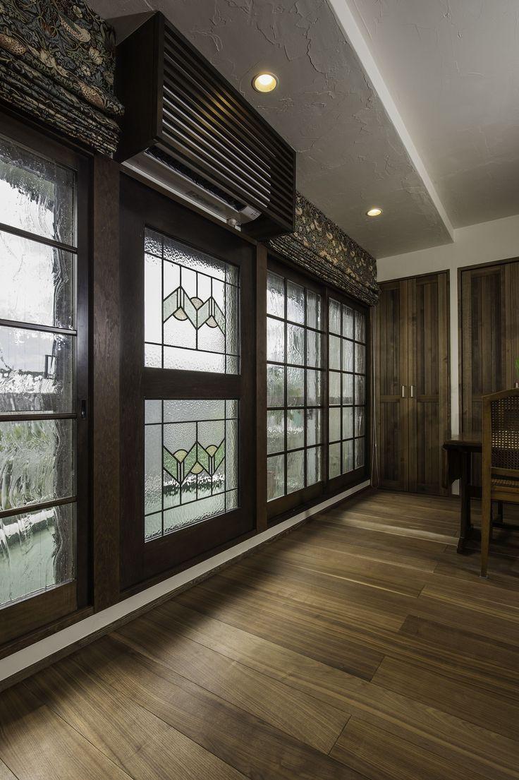掃き出し窓の前にはステンドグラスや気泡入りガラスをはめ込んだ木窓を設置。エアコンも木製のルーバーで目隠ししています。