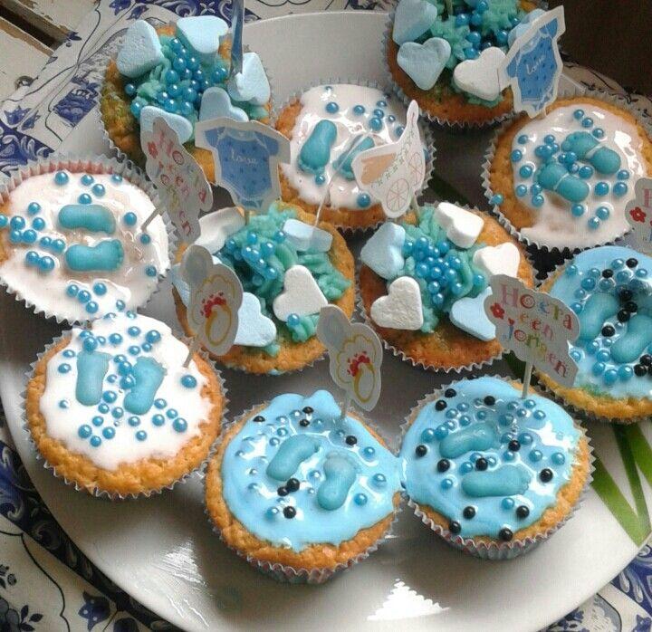 Vanille cupcakes met glazuur, blauwe voetjes van marsepein en diverse versiering. Voor een baby shower gemaakt.