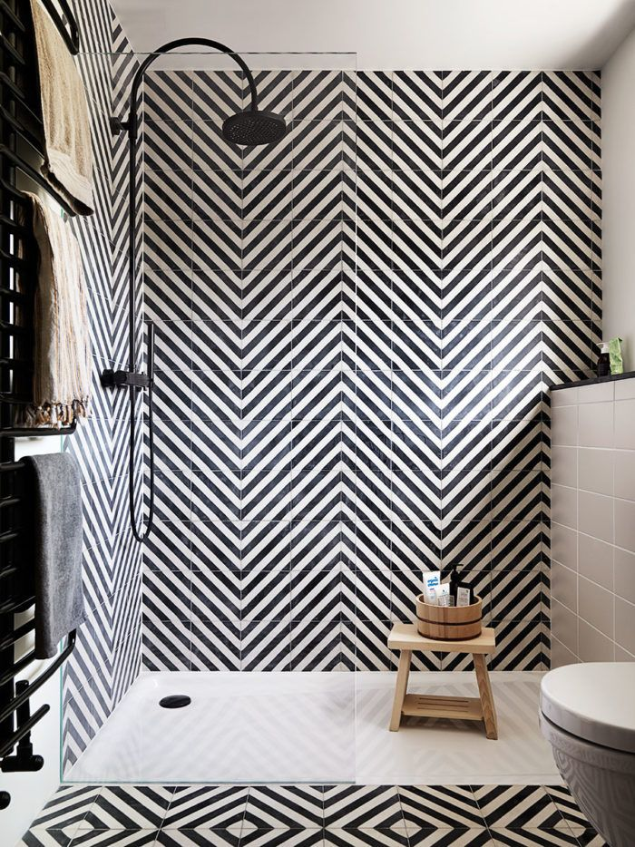 This stylish bathroom has used black and white tiles to create a visually stunning monochrome space.