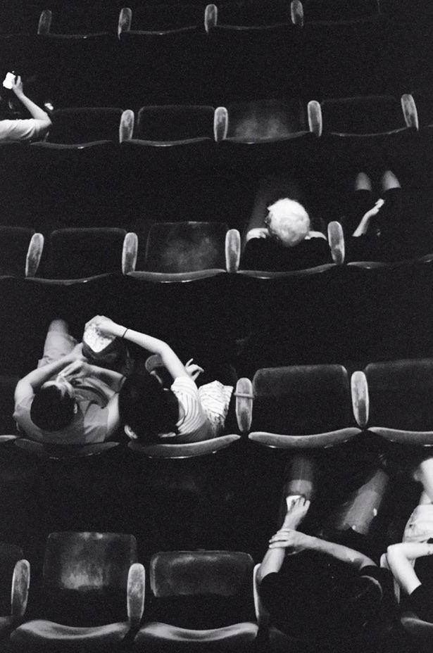 I adore this photo. The empty spaces and mix of ages suggest an art house film. These people are watching a good movie.:
