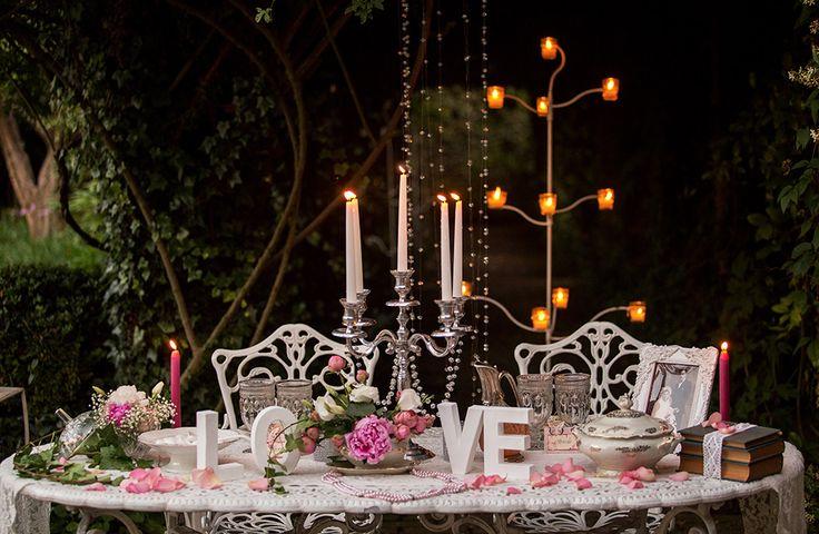Tavolo sposi in ferro battuto bianco coperto con un runner in pizzo antico e decorato con fiori, candelabro con fili di cristallo e scritta LOVE in perfetto stile shabby.