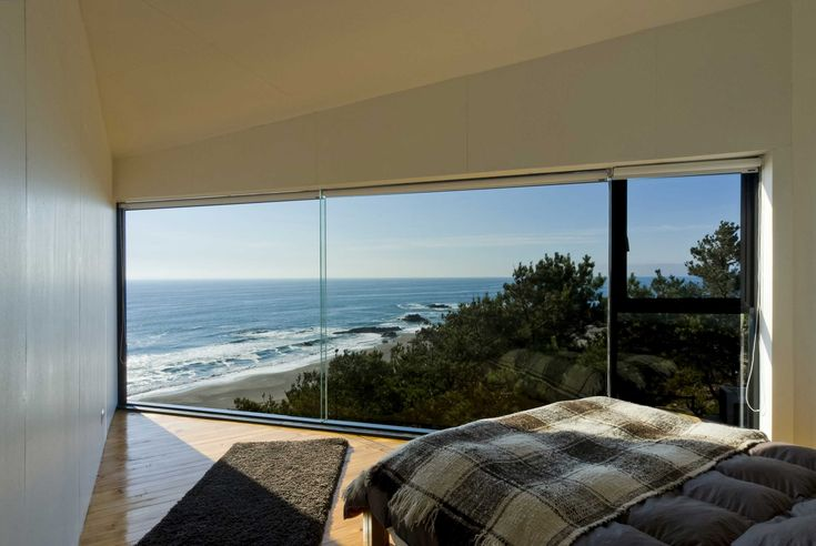 Angular bedroom with a floor-to-ceiling glass wall and ocean view