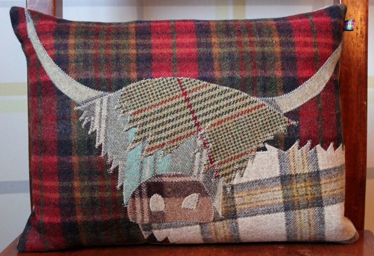 £65.00 Beautiful handmade Highland Cow cushion, filled with a feather pad. This particular Coo is appliquéd onto a rich red, gold and green tartan background. His body is a combination of rich caramels and oatmeal colours. The shaggy fringe is a caramel and red tweed which flops over a duck egg blue and grey face. Topped off with a toffee and chocolate nose and stunning caramel longhorns.