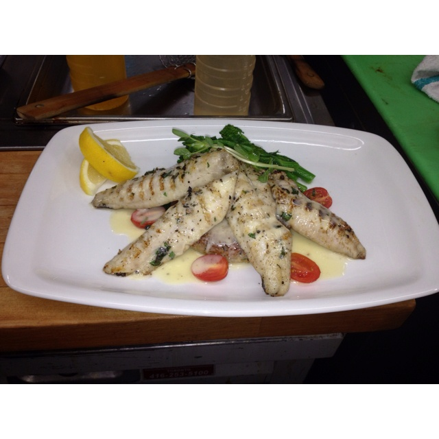 Grilled lake perch with crab potato cake rapini and lemon beurre blanc