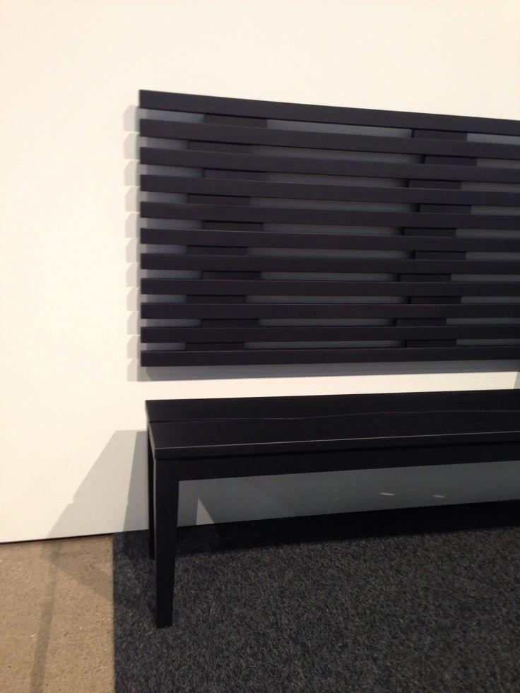 Habitare 2014, Peltola. Upea musta Puro penkki ja seinään kiinnitetty sängynpääty selkänojana.