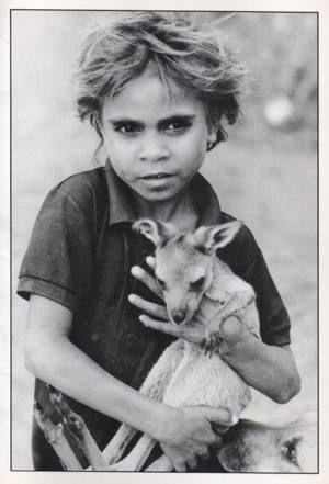 Aboriginal child holding kangaroo Joey • Australian mateship