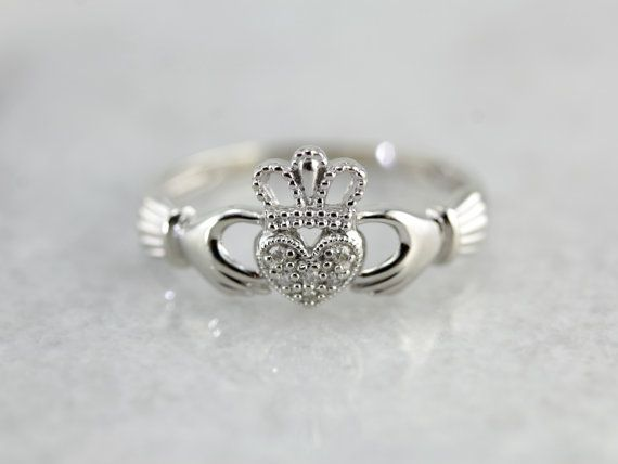 Jolie diamants couvrent la surface de cette bague vintage et la Couronne classique et les mains pavées de petits diamants! L'or blanc lumineux fait un excellent complément pour les diamants exquis!  Bagues de fiançailles représentant deux mains jointes datent de plusieurs siècles dans lhistoire européenne. La version irlandaise, lanneau de Claddagh, a vu le jour dans les années 1600 et ont été produite continuellement depuis cette époque.  Métal : or blanc 10K Gem: 6 diamants ronds…