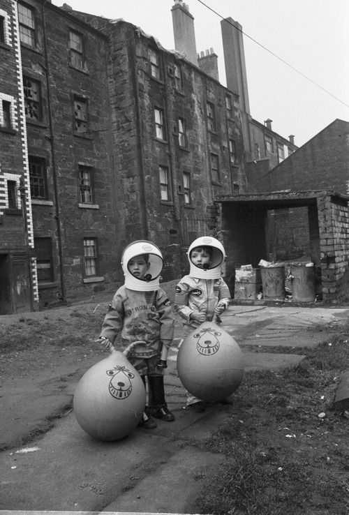 Boys in a Glasgow back court show off their Christmas presents, which include astronaut suits and Space Hoppers. 1970