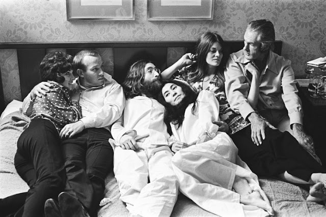 "John Lennon and Yoko Ono during their ""Bed In"" for peace at Montreal's Queen Elizabeth Hotel in June 1969. Here, Tommy Smothers, an unknown friend, John Lennon, Yoko Ono, Rosemary Leary and Timothy Leary."