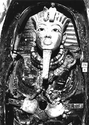 Máscara de Tutankhamón in situ, cubriendo aún la cabeza del faraón, y complementada con llamativos collares. La foto muestra algunos otros objetos, entre los muchos que se colocaron sobre la momia. Se observa también la resina endurecida que dificultó tanto las tareas.
