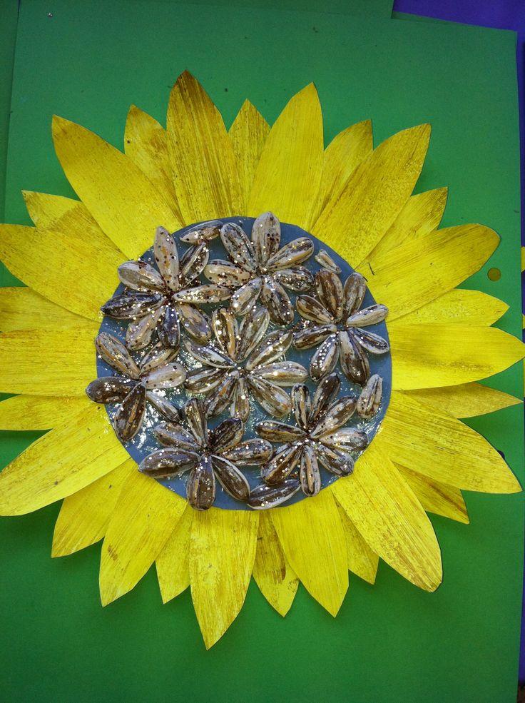 Tapa d'album de gira-sol: es pinta un altre full amb groc, i pinzellades de daurat per sobre; es dibuixen i retallen els pètals i s'enganxen sobreposats. Al cente s'hi enganxen pipes fent la forma que vulguis, i després s'envernissen amb purpurina daurada.