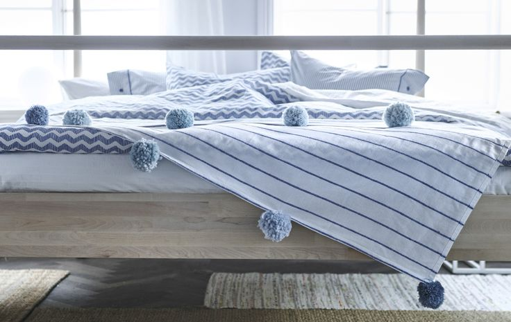 IKEA - Pom pom trim bedspread. A close-up image of blue and white linens on a bed, one with a pom pom trim.