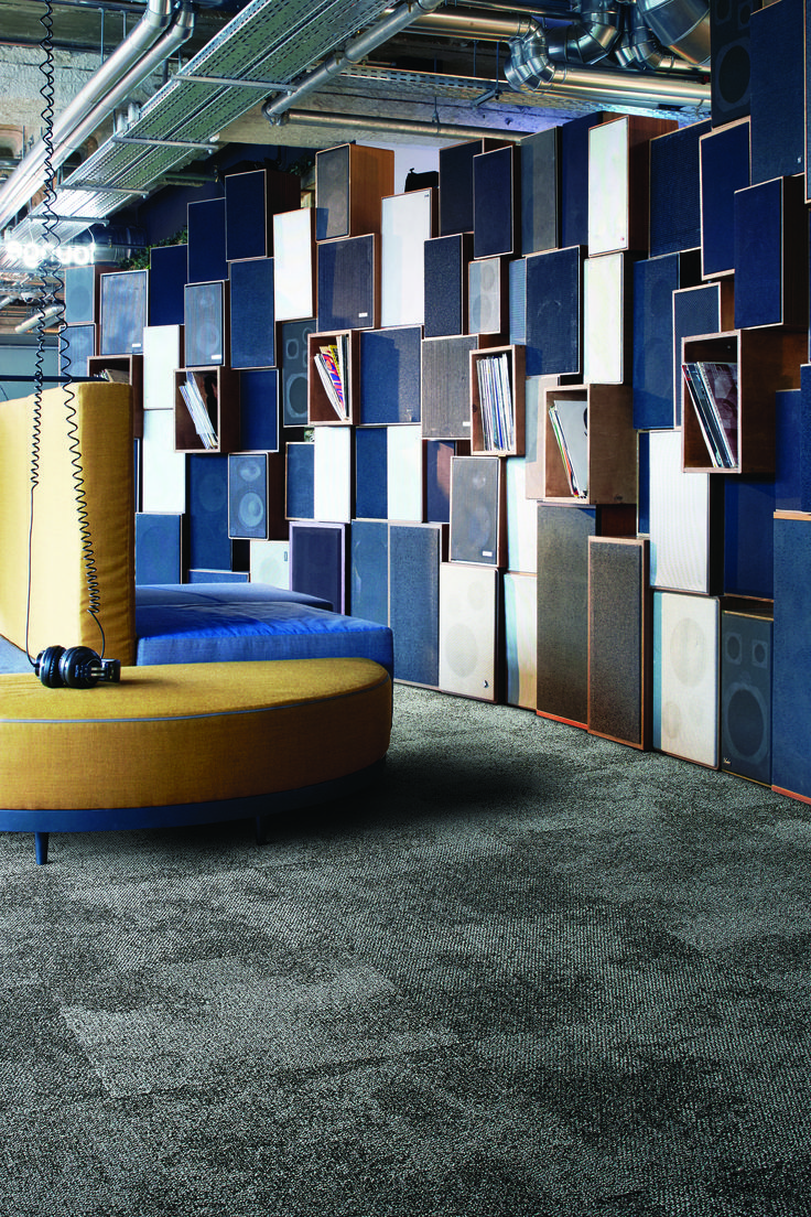 Composure Transcribe. #Interfacecarpets #design #flooring. Dark floor designs for simple, relaxing spaces like this lounge area / collaboration space. Modern wall fixtures and seating fill the commercial space. Yellow and blue interiors add the right amount of color.