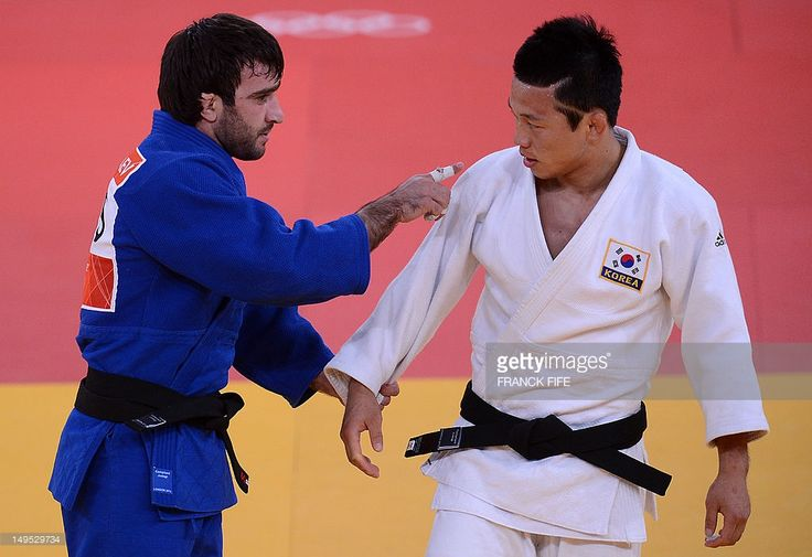 Russia's Mansur Isaev (blue) gestures toward South Korea's Ki-Chun Wang (white) after winning their men's -73kg judo contest semi-final match of the London 2012 Olympic Games on July 30, 2012 at the ExCel arena in London.