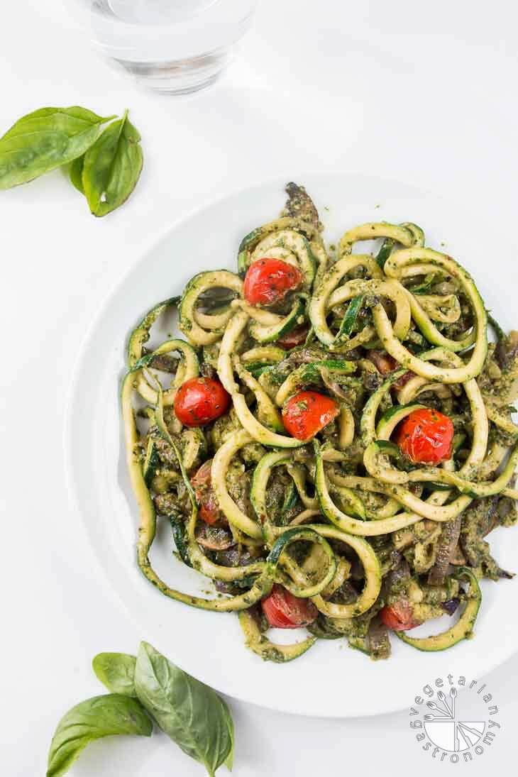Overhead photograph of pesto zucchini spaghetti recipe on a white plate with a glass of water and fresh basil leaves off to the side.