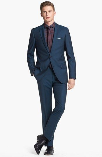 Hugo Boss two buttons navy blue suit. Simple but timeless design with a classic blue color makes a totally office look. Also, the pocket design is very nice and chic. This suit makes a very formal look, serious and professional.