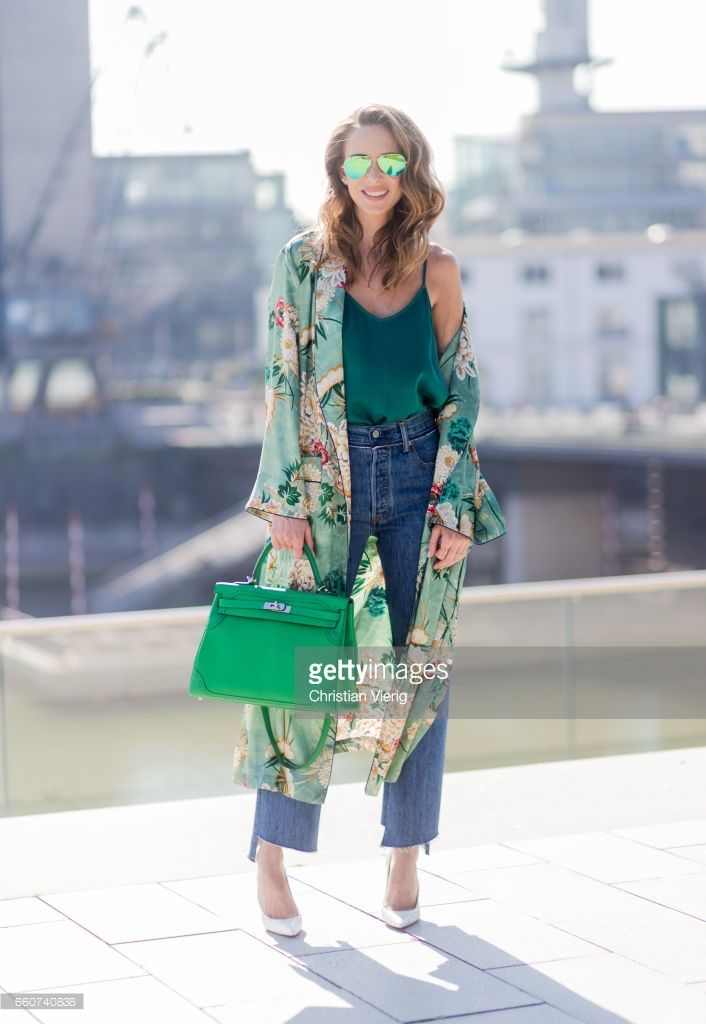 Model and fashion blogger Alexandra Lapp wearing wearing a green flower printed kimono from Zara, a green tank top in silk, blue jeans from Vetements in cooperation with Levi´s with cut-out raw hems, white snake pumps from Christian Louboutin, Ray Ban Aviator sunglasses in green and a Hermes Kelly Ghillies 35 bag in green bamboo on March 30, 2017 in Duesseldorf, Germany.