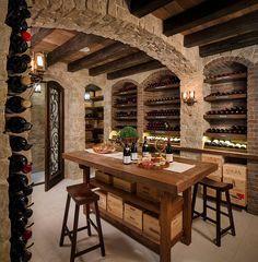Mediterranean wine cellar and tasting room with stone walls [Design: KW Designs]